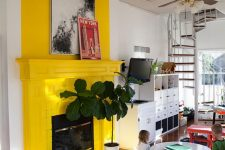 12 a sunny yellow fireplace and mantel with some artworks and a plant next to it create a sunny and shiny mood in the room