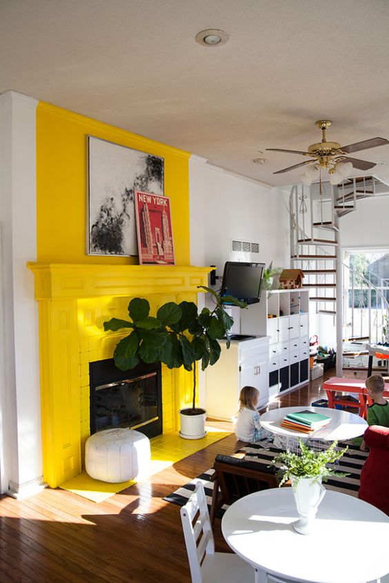 a sunny yellow fireplace and mantel with some artworks and a plant next to it create a sunny and shiny mood in the room