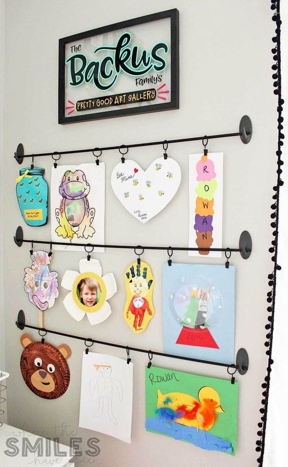 a bold kids' artwork display with railings is a stylish and cool idea and you may add more and more works there