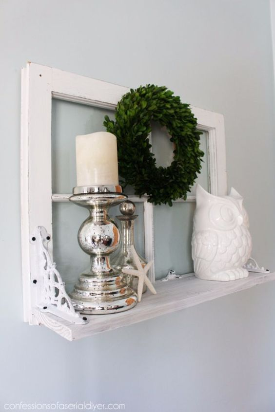 a small shelf with an old window frame as a base, mercury glass candleholders, a greenery wreath, an old is a stylish decoration for a vintage space