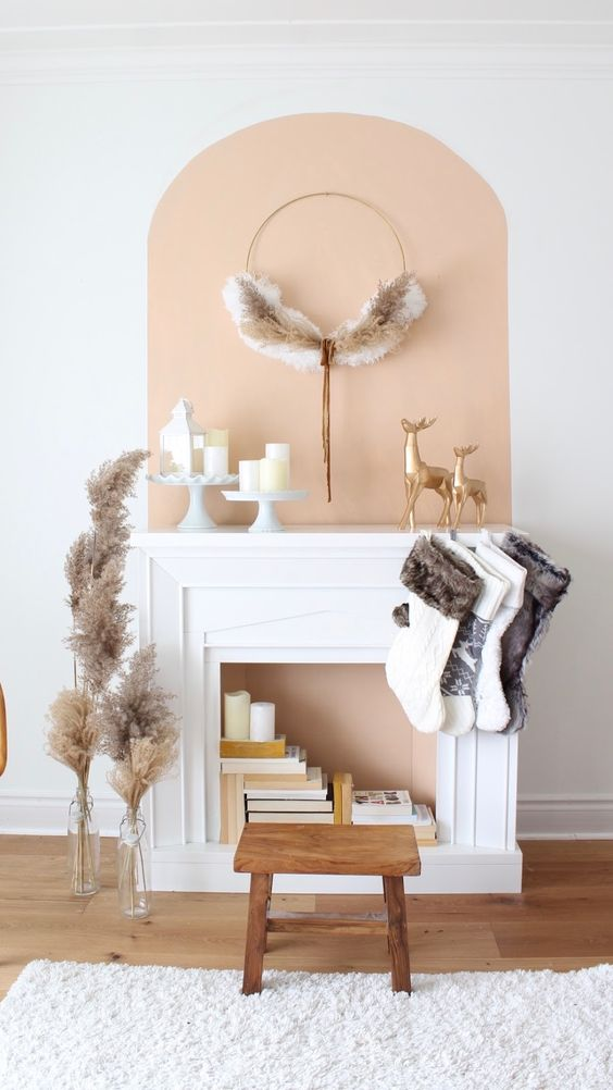 a faux fireplace with a peachy inside, books and candles and stockings and a wreath for Christmas