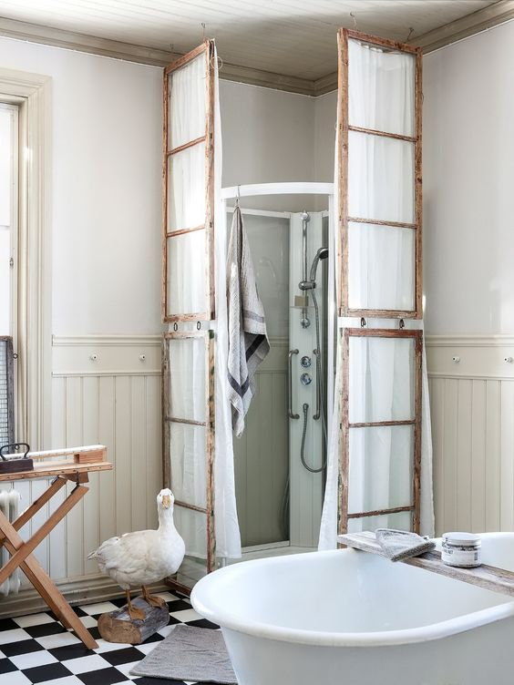 a vintage bathroom with a modern shower space but clad with old window frames and with white fabric hanging