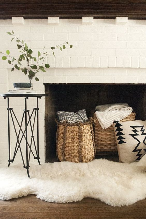 a white brick fireplace with baskets with pillows and throws, white faux fur for a cozy farmhouse space