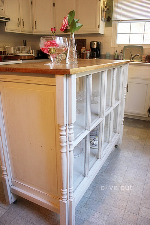 a vintage kitchen island with inner shelves and window frames covering them is a stylish idea with a refined feel