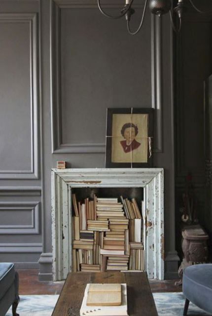 a shabby chic fireplace clad with a refined old picture frame and with lots of books inside is a refined and bold idea