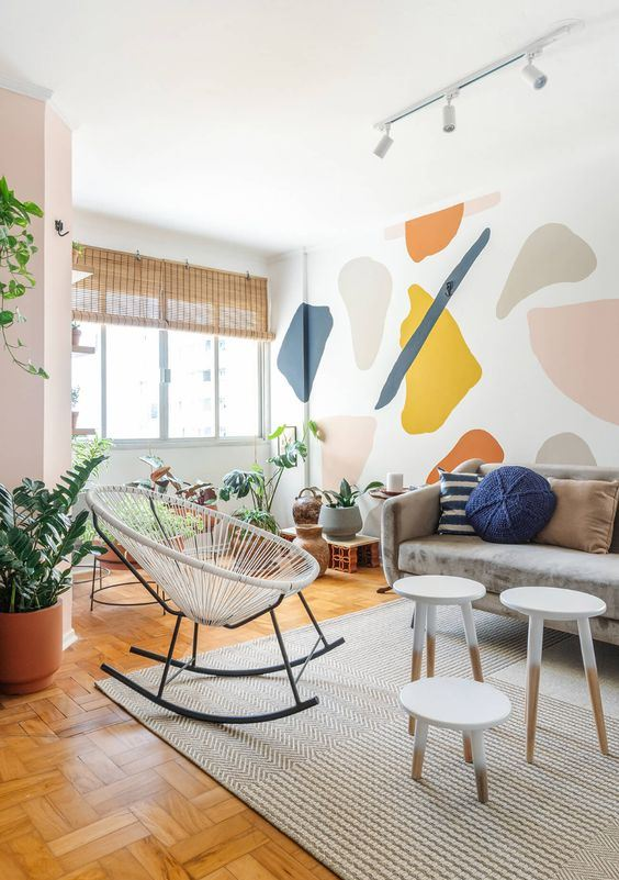 a modern and airy living room with a bold terrazzo accent wall that brings a fun and colorful touch to the space