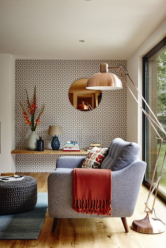 a reading nook highlighted with geometric wallpaper that highlights the mid century modern decor of the room