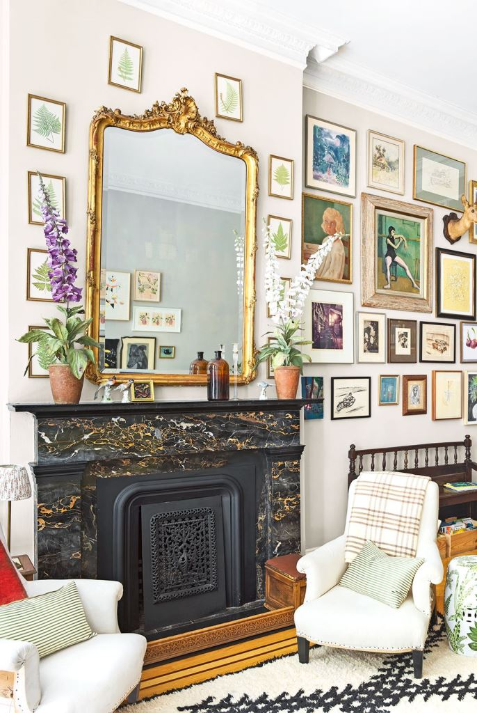 a refined black, white and gold fireplace with a beautiful and refined cover and a gorgeous vintage mirror over it