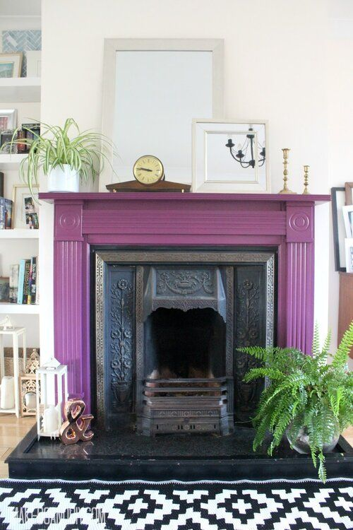 a vintage fireplace with a purple mantel around, some potted plants, candle lanterns and mirrors