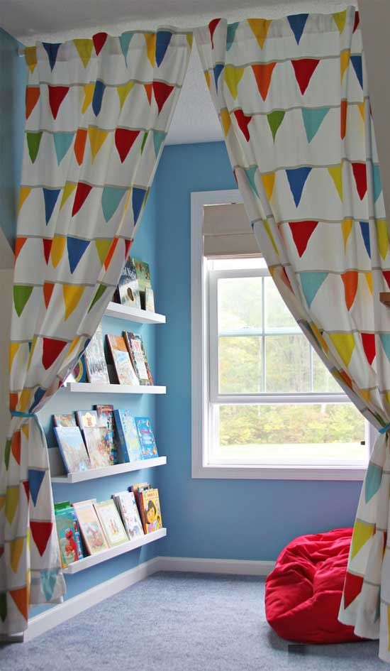 a colorful reading nook with a bright seat by the window and ledges on the wall is separated with colorful curtains