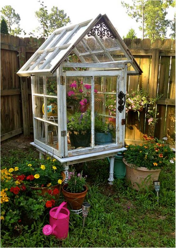 a large greenhouse with lots of planters built completely of old window frames and with bright blooms inside is very nice for outdoors