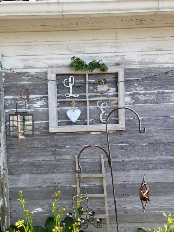 a pretty and easy rustic artwork made of an old window frame, some wooden letters, a wreath and a heart plus greenery can be used indoors and outdoors