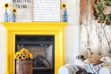 25 a sunny yellow fireplace, a bold blue ottoman and blue bottles with sunflowers to make the space bolder
