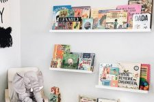 26 a contemporary reading nook with white and light stained furniture, bold books and toys