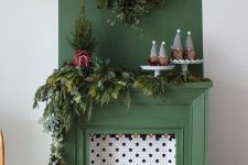 26 a green non-working fireplace with hex tiles and candles inside, with lush evergreens for Christmas