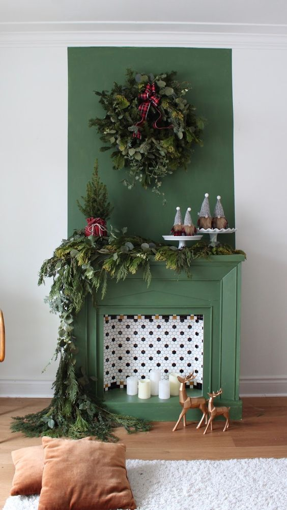 a green non-working fireplace with hex tiles and candles inside, with lush evergreens for Christmas