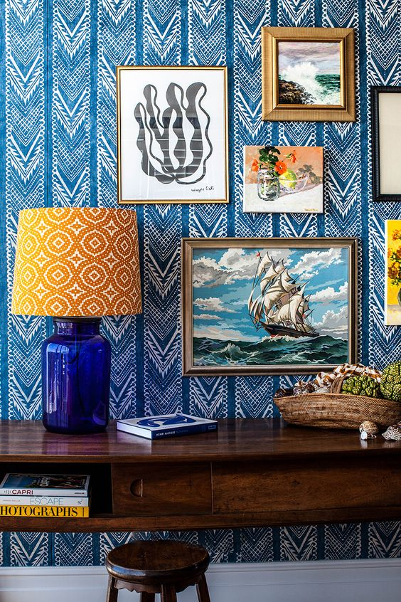 refined bold blue and white printed wallpaper and a gallery wall on it plus a printed lamp for a bright and eye catchy nook