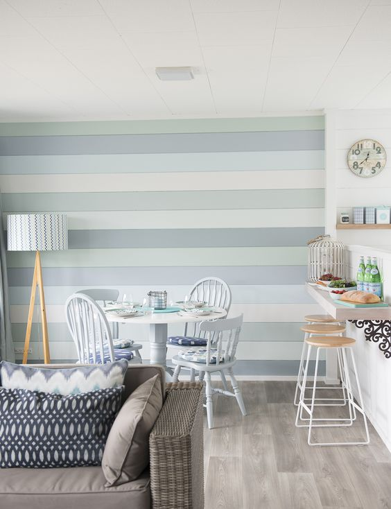 a beach space with a small breakfast bar, a dining space and a living room and a coastal-colored accent wall for a statement