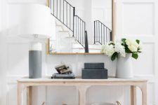 a chic modern entry with a large mirror, a pretty wooden console with baskets and a color block lamp is simple and stylish