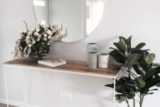 a chic modern entry with a wooden console, a round mirror and some potted plants and vases