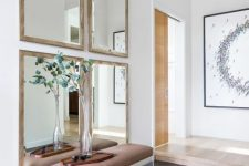 a chic modern entryway with a gallery wall of mirrors, a leather and acrylic bench and greenery in a vase