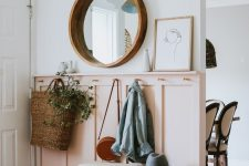 a chic modern entryway with a pink paneled wall, a round mirror, a pinhair leg bench and baskets