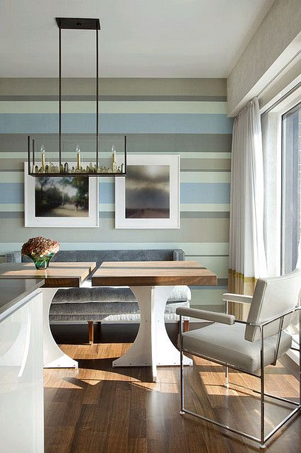 a coastal dining room with a unique striped wall in coastal colors, neutral furniture, color block curtains and a unique chandelier