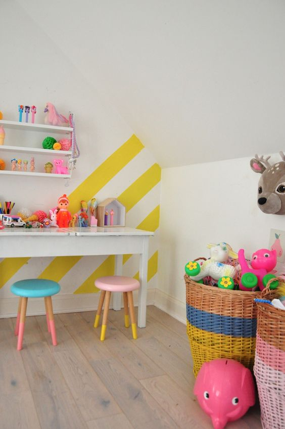 a colorful kids' playroom accented with a yellow and white striped wall and lots of bold toys