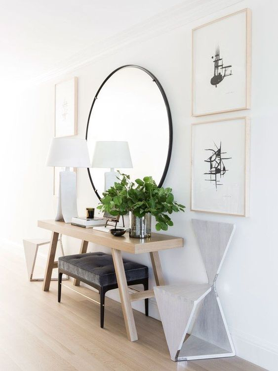 a modern entry with a round mirror, a wooden console, an upholstered ottoman, matching geometric chairs and greenery