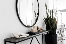 a modern entryway with a black narrow console, a round mirror, a statement plant and some decor
