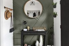 a modern entryway with a green paneled wall, a black console, some railings and planters on the wall