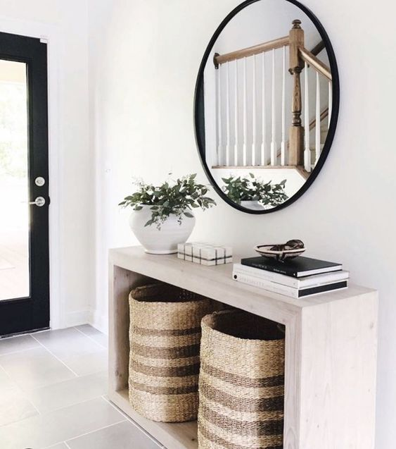 a modern entryway with a sleek wooden console, baskets for storage, a round mirror and a potted plant