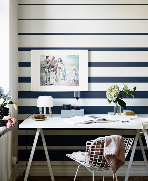 a modern home office with a striped navy and white striped wall, a trestle desk and a white metal chair