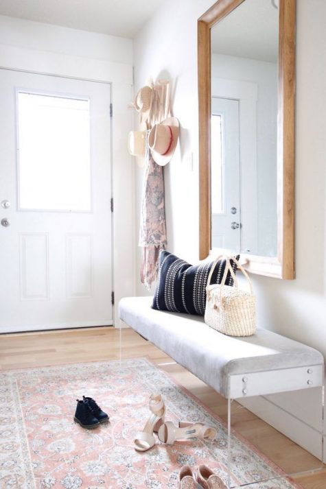a modern light-filled entryway with a bench with acrylic legs, a statement mirror, a boho rug and a clothes rack