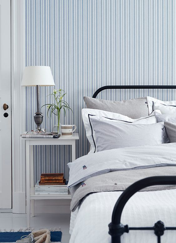 a retro coastal bedroom with a blue and white striped wall. a black metal bed and a white nightstand plus a vintage lamp