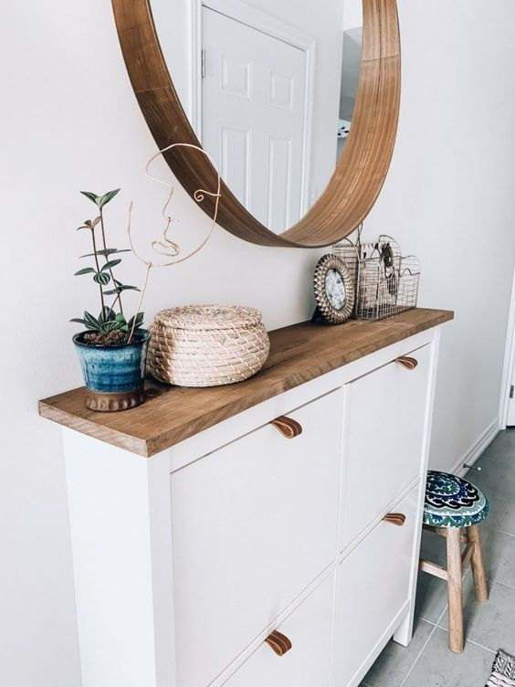 a stylish modern entry with an IKEA shoe cabinet hacked, a round mirror and a potted plant