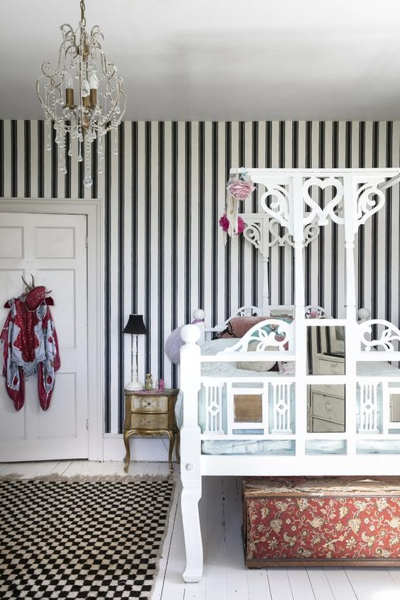 a super refined bedroom with a black and white striped wall, a unique carved bed, a beautiful crystal chandelier and exquisite furniture