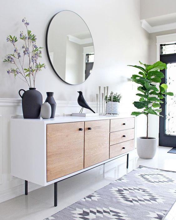 an airy modern entryway with a mid-century modern sideboard, a round mirror, a statement plant and some decor