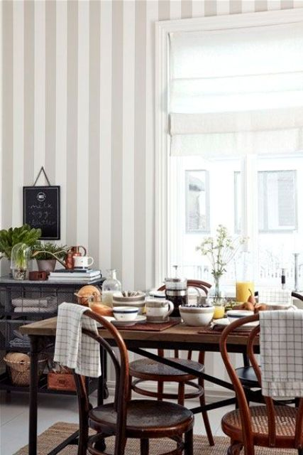 an ethereal vintage-inspired dining room with a grey and white striped wall, dark stained furniture and potted plants and blooms