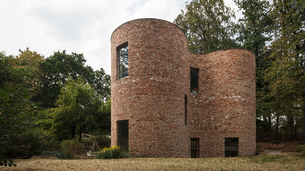 This unique house in Belgium is built of reclaimed bricks and is dotted with large windows here and there also featuring a gorgeous shape