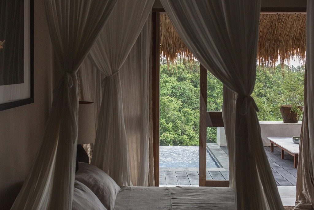 The bedroom is done in pure neutrals, with a comfy bed and gorgeous views