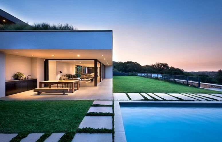 The house is built for outdoor-indoor living, there's a lawn terrace and a pool outside