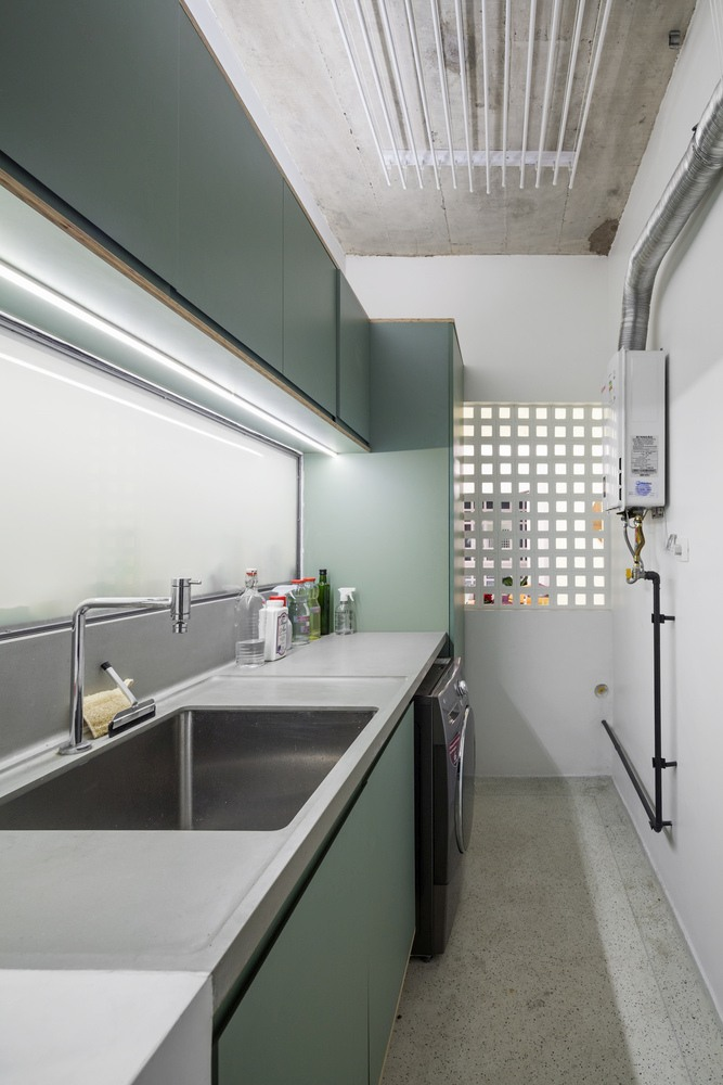 The laundry features sleek green cabinets and concrete countertops just like the kitchen