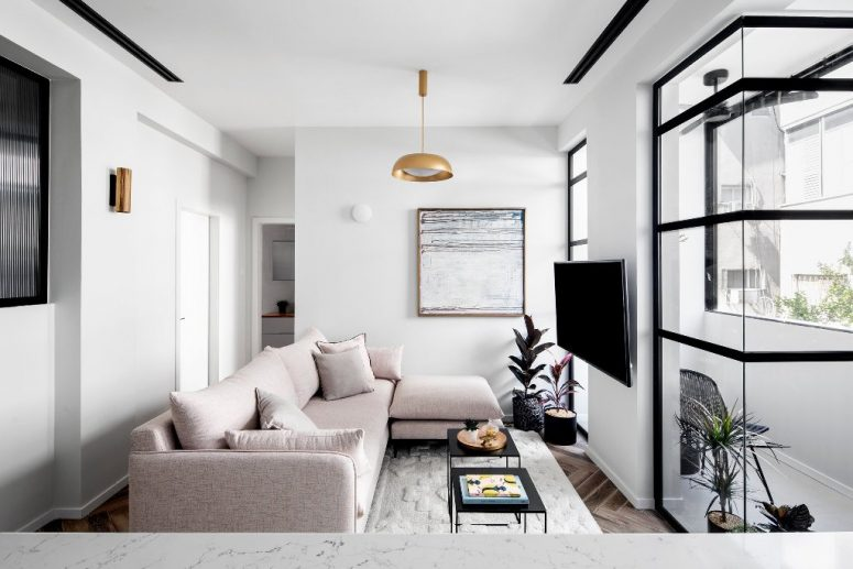 The living room features a blush sectional, a statement artwork, brass touches and an entrance to the balcony