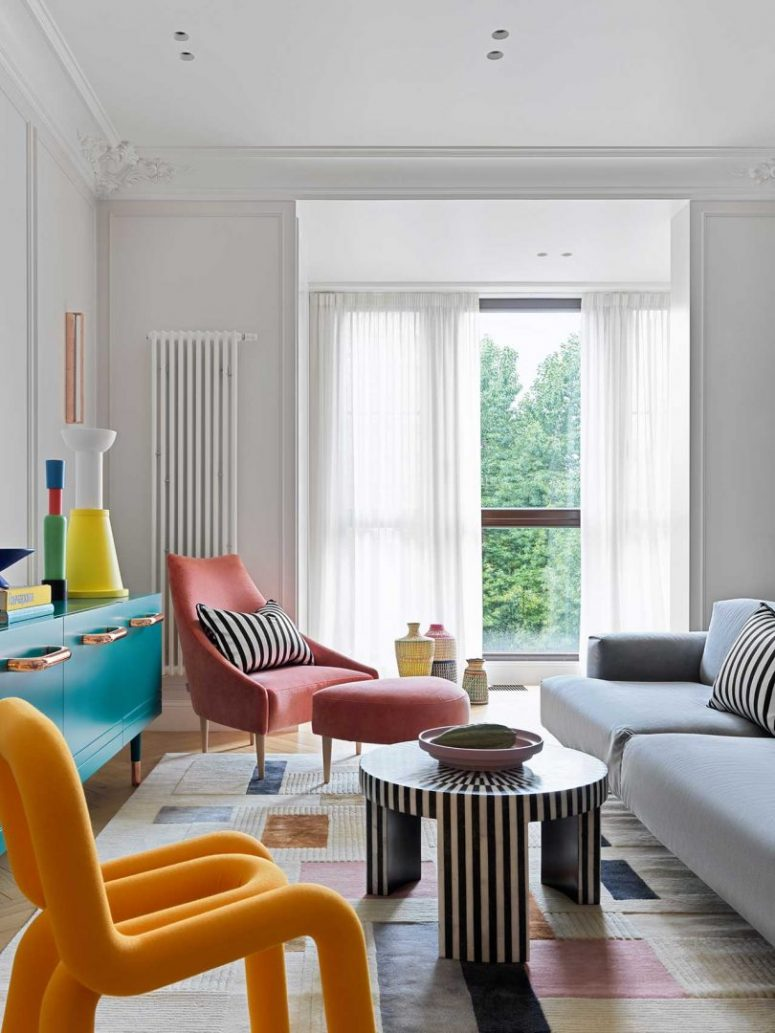 The living room features colorful furniture and objects, striped accents and bold accessories