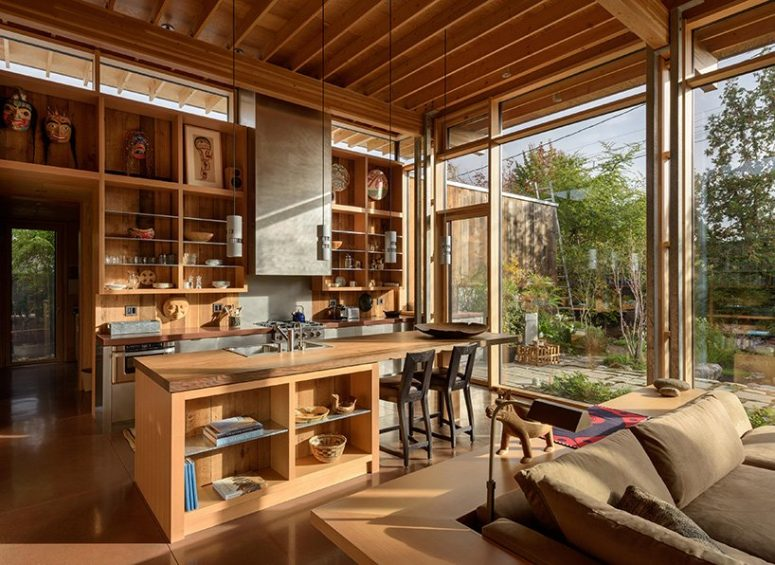 The main layout comprises a kitchen, a living and dining space and is filled with natural light coming through glazed walls