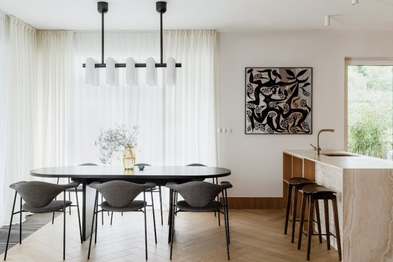The kitchen and dining space are united into one layout, with chic furniture, quirky art and bold lamps