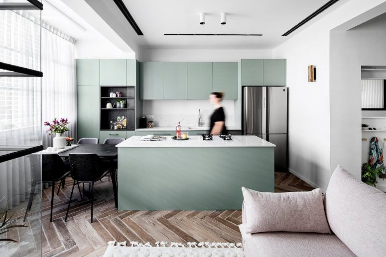 The kitchen and dining zone are also here, the cabinets are green ones, with mable countertops and a backsplash, a black dining table and chairs