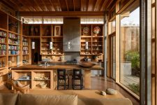 03 The kitchen is done with lots of open shelving and a large kitchen island of wood with a place for meals