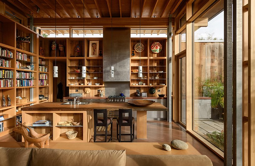 The kitchen is done with lots of open shelving and a large kitchen island of wood with a place for meals